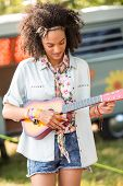 picture of ukulele  - Pretty hipster playing the ukulele on a sunny day - JPG