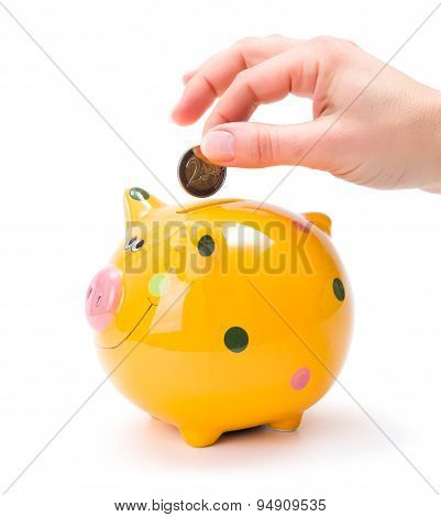 Hand Putting A Coin Into Piggy-bank