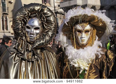 Masked Persons In Golden Costume On San Marco Square In Venice, Italy.