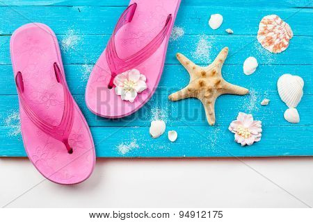 Summer accessories on blue wooden background.