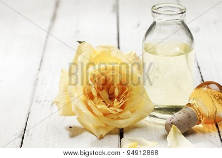 Yellow rose blossom and bottle of extract on rustic background