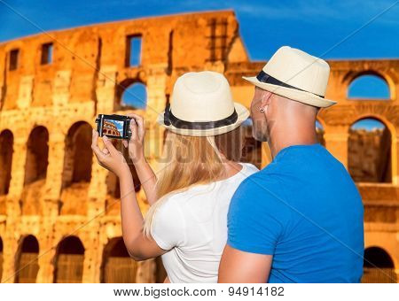 Back side of young happy couple taking picture of beautiful gorgeous ancient Coliseum, honeymoon vacation in Rome, Italy, Europe