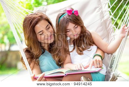 Portrait of beautiful mother with cute little daughter sitting on backyard in hammock and reading interesting book, spending wonderful summer holidays together