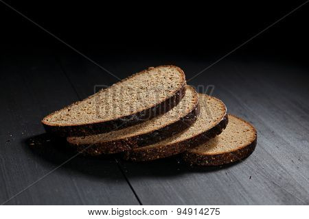 Sliced black bread on wooden table close-up