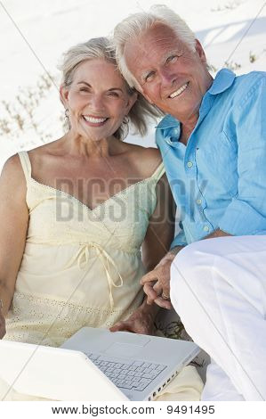 Happy Senior Couple Using Laptop Computer On A Beach