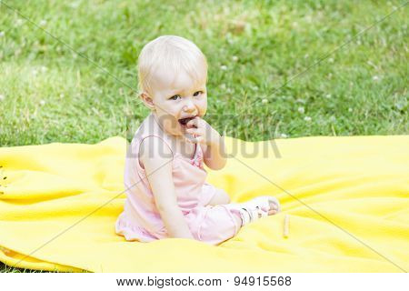 toddler girl wearing pink dress sitting on blanket
