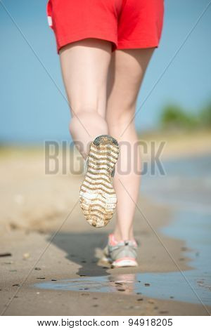 Sport footwear, sand footprints and legs close up. Runner feet d