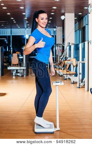 Happy Woman smiling on weighing scales at gym