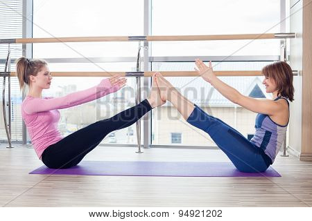 Aerobics Pilates personal trainer helping women group in a gym c