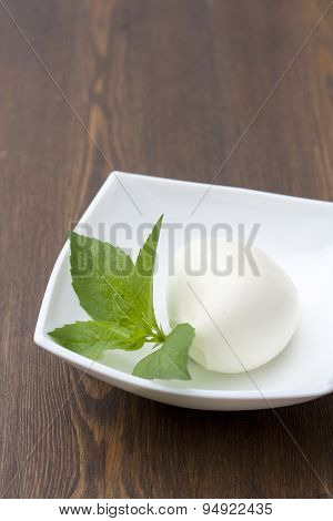 Mozzarella with herbs in a white rectangular bowl on wooden table
