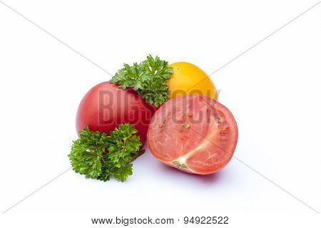 Red and yellow tomato and parsley on the white isolatd background