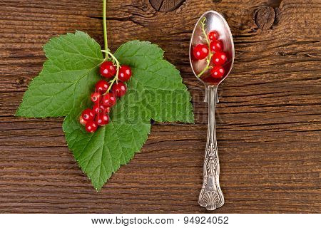 redcurrant silver spoon with leaf over vintage background
