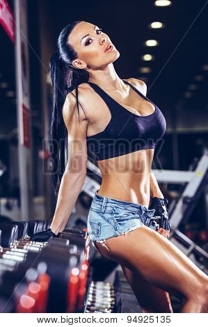 sexy young girl resting after dumbbells exercises.
