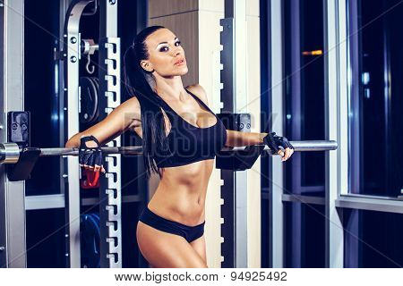 Woman resting after lifting barbell in gym