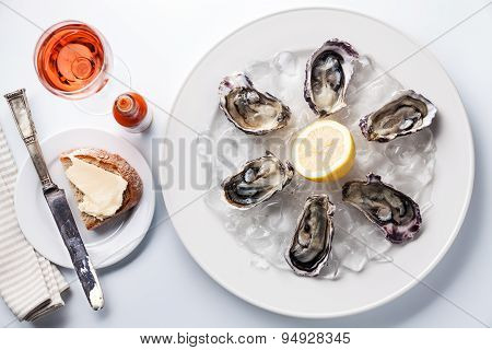 Opened Oysters On White Plate, Rose Wine And Dark Bread With Butter On White Background