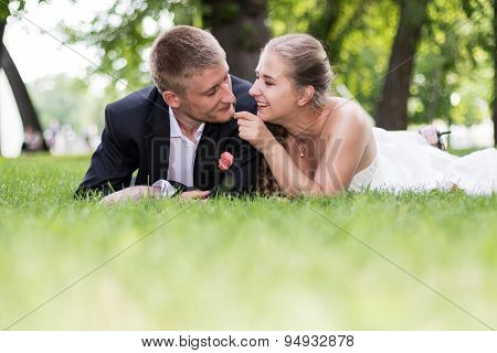 Bride and groom playing in the grass