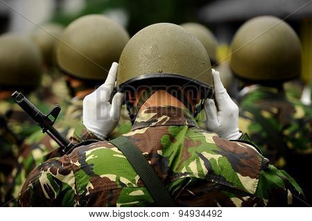 Soldier In Camouflage Uniform Arranging His Helmet