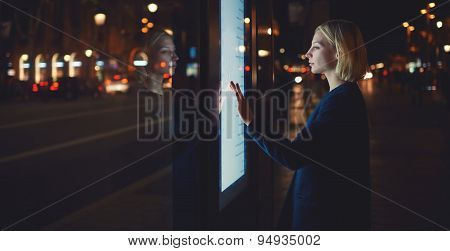 Woman using modern urban application of bus stop in Barcelona for find out schedule of transport