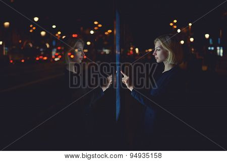 Beautiful female using automated teller machine with big digital screen while standing in night city