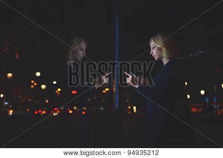 Caucasian young female touching big digital display with reflected on her screen light