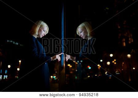 Young female doing internet money payment with automated teller machine in night city