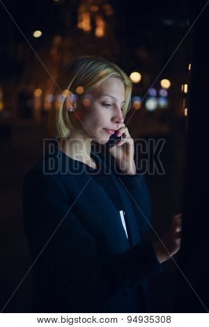 Young business woman speaking on smartphone while standing in night city with out-of-focus