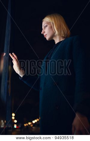 Charming young female touching big digital display with reflected on her screen light