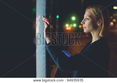 Gorgeous caucasian businesswoman touching sensitive screen of smart city bus stop in night city