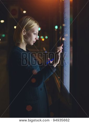 Attractive young woman touching big digital information screen while standing on train platform