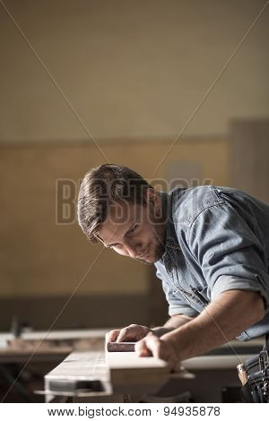 Carpenter Sanding Wooden Plank