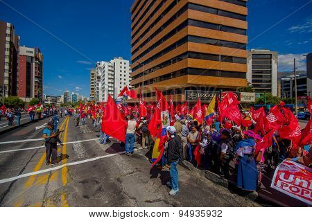Protesters with red flags from Union Popular party marching in the capital city Quito against govern