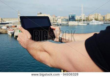 Male tourist photographing marina port city with touch pad during vacation holidays memories