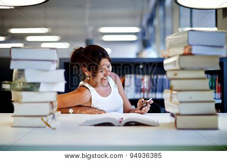 Working hard for great grades asian smiling student using imobile phone in university library