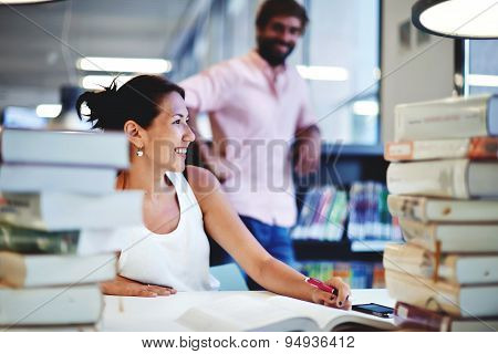 Smiling college student sitting at the desk with huge pile of study book in university library