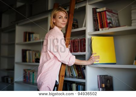 Girl architect holding modern book of her collection while standing on wooden ladder at her home