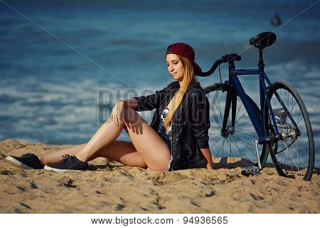 ?harming young female with rental bike sitting on the beach while enjoying the sea waves