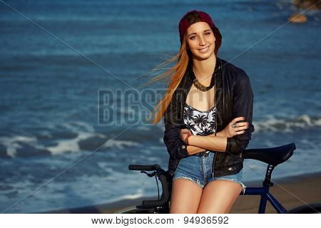 Attractive cute hipster girl leaning on her bicycle while relaxing after ride along seashore