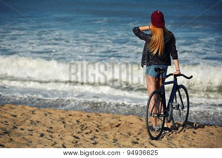 Young woman standing on seashore enjoying sea view at holiday after ride on her sport bicycle