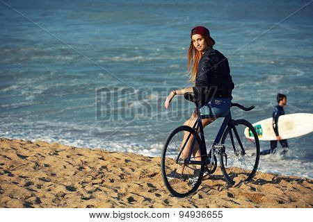Young woman standing on seashore enjoying sunny afternoon after ride on her sport fixed gear bicycle