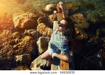 Young woman posing with her skateboard in front of the sea while enjoying summer sunshine