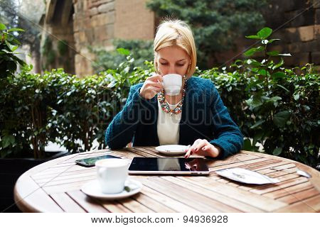 Young attractive businesswoman at coffee time working on digital tablet while sitting of coffee shop