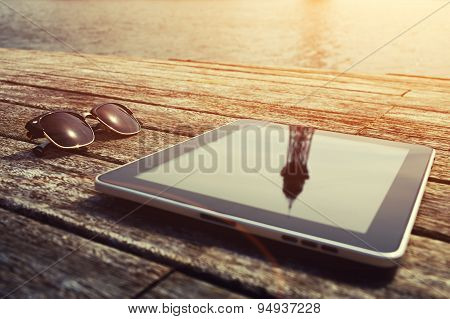 Sunglases and digital tablet lying on wooden jetty at sunny day