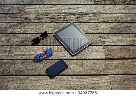 Blank screen digital tablet smart phone and couple of sunglases lying on the wooden texture