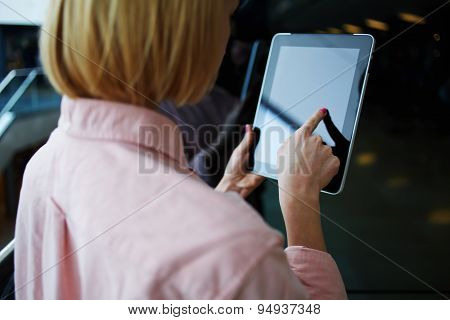 Young successful business woman or freelancer using her wireless devices in modern office