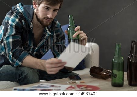 Man Drinking Alcohol And Looking At Photos