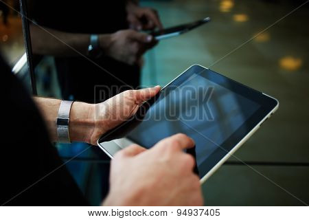 Cropped shot of man's hand typing text message zooming digital image on touchpad