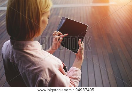 Close up young blonde female student using touchpad with big copy space against wooden background