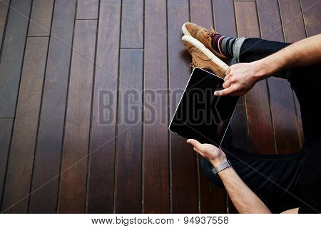 Top view male student using touchpad with big copy space while sitting on wooden floor