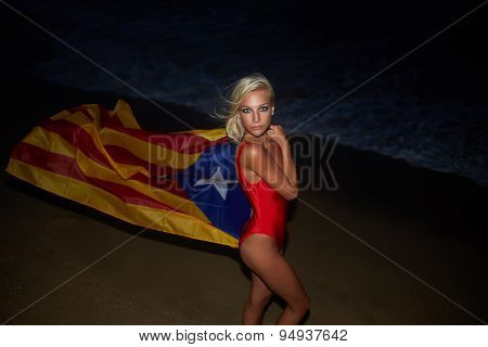 Caucasian blond hair girl with beautiful figure dressed in red swimsuit at sea coastline