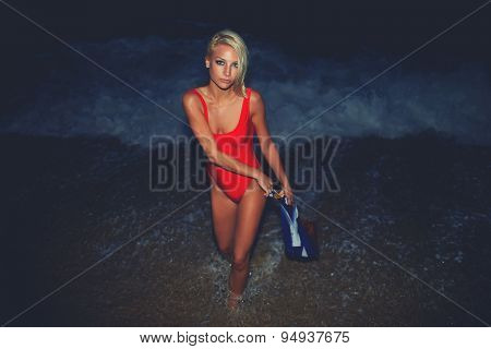 Sexy model with beautiful figure dressed in red swimsuit posing on the ocean beach at night